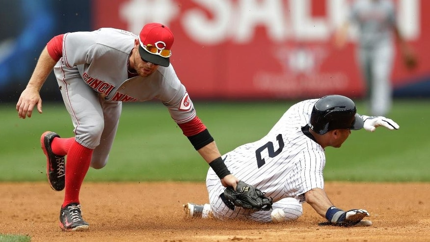 New York Yankees' Derek Jeter (2) steals second base as Cincinnati Reds shortstop Zack Cozart misses the ball while making the tag during the fifth inning of a baseball game, Saturday, July 19, 2014, at Yankee Stadium in New York. (AP Photo/Julio Cortez)
