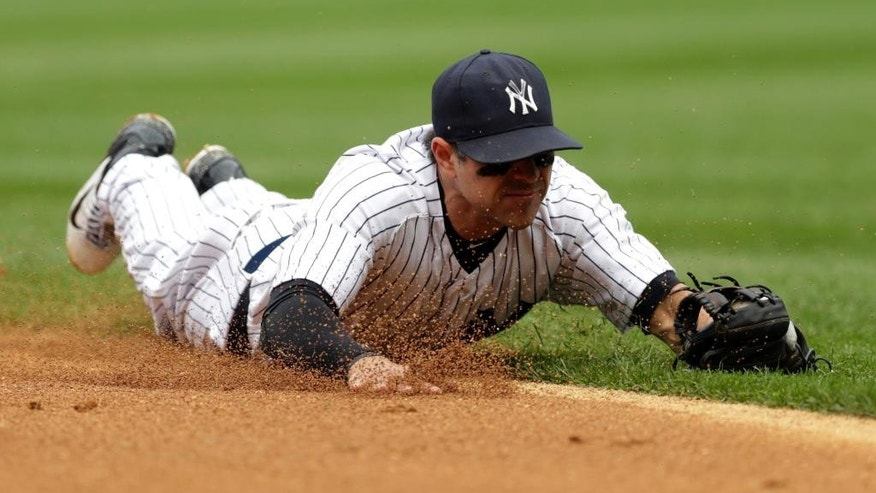 New York Yankees second baseman Brian Roberts makes a diving stop on a ground ball hit by Cincinnati Reds' Billy Hamilton during the fifth inning of a baseball game, Saturday, July 19, 2014, at Yankee Stadium in New York. Hamilton was out at first on the play. (AP Photo/Julio Cortez)