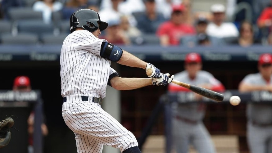 New York Yankees' Brett Gardner gets a hit off Cincinnati Reds starting pitcher Alfredo Simon during the third inning of a baseball game, Saturday, July 19, 2014, at Yankee Stadium in New York. Yankees' Brian Roberts scored on the play. (AP Photo/Julio Cortez)