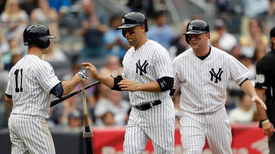 New York Yankees' Carlos Beltran, center, and Brian McCann, right, are congratulated by teammate Brett Gardner, left, after they scored on an RBI single by Kelly Johnson during the sixth inning of a baseball game against the Cincinnati Reds, Saturday, July 19, 2014, at Yankee Stadium in New York. (AP Photo/Julio Cortez)