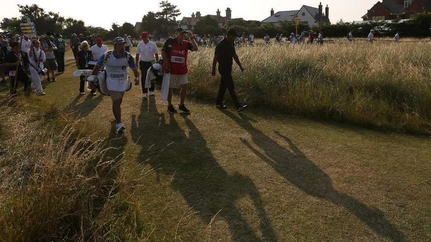 Tiger Woods of the US walks off the 18th hole after finishing his round on the second day of the British Open Golf championship at the Royal Liverpool golf club, Hoylake, England, Friday July 18, 2014. (AP Photo/Jon Super)