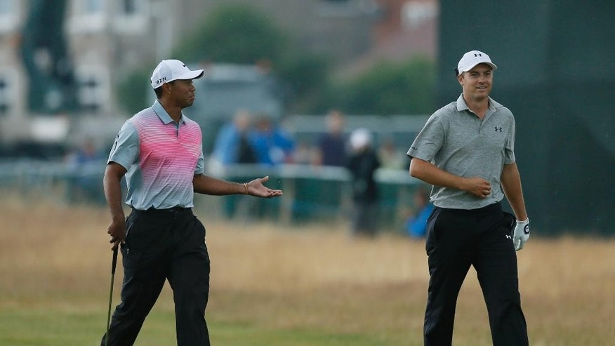 Tiger Woods of the US, left, walks along the 18th fairway with Jordan Spieth of the US during the third day of the British Open Golf championship at the Royal Liverpool golf club, Hoylake, England, Saturday July 19, 2014. (AP Photo/Alastair Grant)