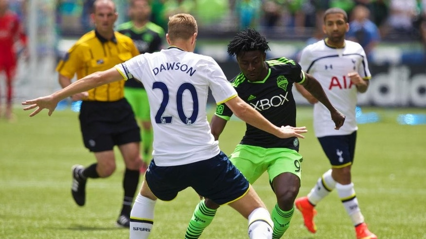 Seattle Sounders' Obafemi Martins (9) tries to get past Tottenham Hotspur's Michael Dawson during the first half of a friendly soccer match in Seattle, Saturday, July 19, 2014. (AP Photo/Stephen Brashear)