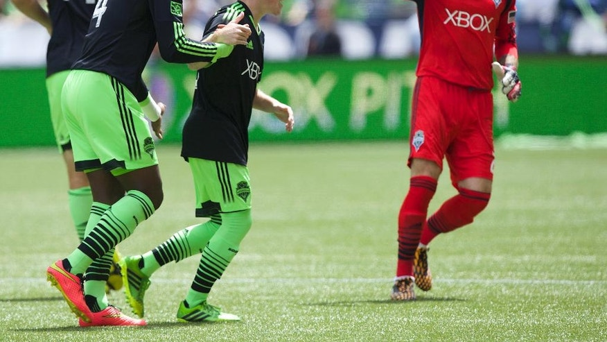 Seattle Sounders' Xander Bailey, second from right, is congratulated by teammates Chad Marshall (14), Jalil Anibaba, second from left, and Stefan Frei after scoring a ceremonial first goal against Tottenham Hotspur before a friendly soccer match in Seattle, Saturday, July 19, 2014. Bailey was signed to the Sounders for the match as part of the Make-A-Wish program. (AP Photo/Stephen Brashear)