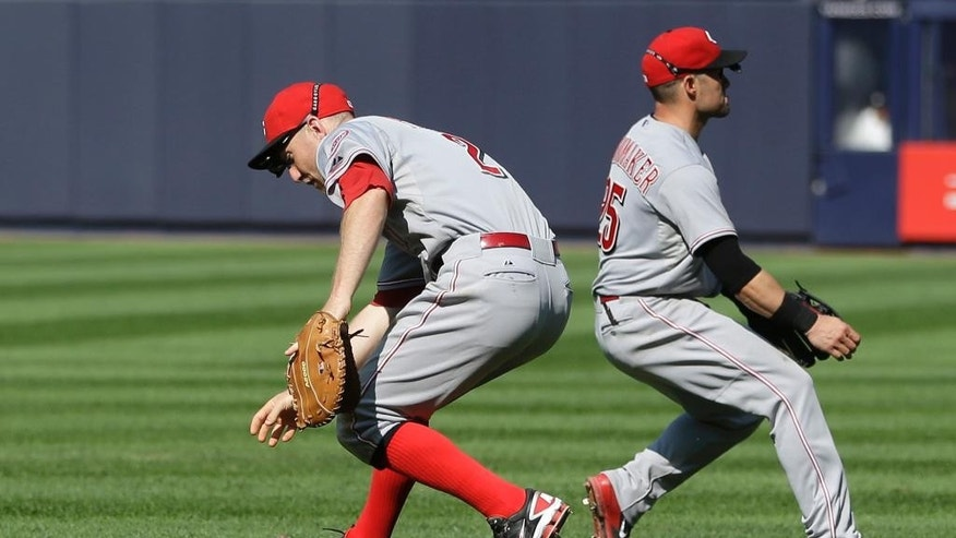 CORRECTS TO FIRST BASEMAN, TODD FRAZIER, LEFT, AND SECOND BASEMAN SKIP SCHUMAKER -Cincinnati Reds first baseman, Todd Frazier, left, and second baseman Skip Schumaker chase after a ball hit by New York Yankees' Brian McCann during the ninth inning of the game at Yankee Stadium Sunday, July 20, 2014 in New York. The hit scored the winning run and the Yankees defeated the Reds 3-2. (AP Photo/Seth Wenig)