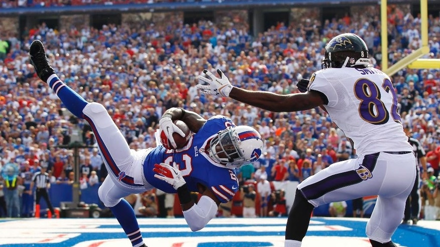 "File-This Sept. 29, 2013, file photo shows Buffalo Bills free safety Aaron Williams (23) intercepting a pass intended for Baltimore Ravens wide receiver Torrey Smith (82) during the second half of an NFL football game in Orchard Park, N.Y. Going on his fourth year in Buffalo, Williams is all too familiar with the cycle of emotions Bills players and fans endure during a season. ""Every year, everybody gets hyped up for an incredible season and then people get let down with a six-win season,"" Williams said, upon reporting for the start of camp. ""To me, I'm getting tired of it.""  (AP Photo/Bill Wippert, File)"
