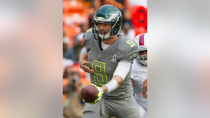 File-This Jan. 26, 2014, file photo shows Philadelphia Eagles quarterback Nick Foles  of Team Sanders looking to hand of the football in the third quarter quarter of the NFL Pro Bowl football game in Honolulu. Foles' emergence from backup to Pro Bowl MVP was the key to Philadelphia's success last season. It also was one of the year's biggest surprises, considering Foles lost the starting job to Michael Vick in training camp, and wasn't thought to be a fit for Kelly's up-tempo offense. But a guy who throws 29 TDs and only two interceptions and has a 119.2 passer rating will fit into any system. (AP Photo/Eugene Tanner, File)