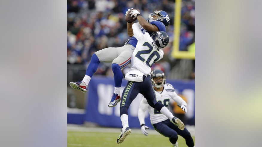 File-This Dec. 15, 2013, file photo shows New York Giants wide receiver Victor Cruz, left, making a catch as Seattle Seahawks cornerback Jeremy Lane defends on the play during the second half of an NFL football game,  in East Rutherford, N.J. One of Eli Manning's favorite wideouts, Hakeem Nicks, signed with Indianapolis. His other top target, Cruz, is back and provides the QB a comfort zone, along with 75 or so receptions.(AP Photo/Kathy Willens, File)