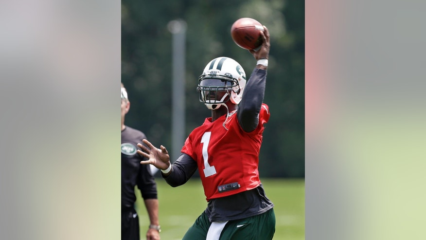 File-This June 17, 2014, file photo shows New York Jets quarterback Michael Vick throwing a pass during NFL football minicamp  in Florham Park, N.J. Vick was signed to give the Jets an experienced backup option to Smith, in case the second-year QB struggles or gets injured. Vick is familiar with offensive coordinator Marty Mornhinweg's system from their days together in Philadelphia, and believes he has a lot more left. But Smith, coming off a season in which he had 12 TD passes and 21 INTs, enters training camp with the edge for the starting job. (AP Photo/Mel Evans, File)