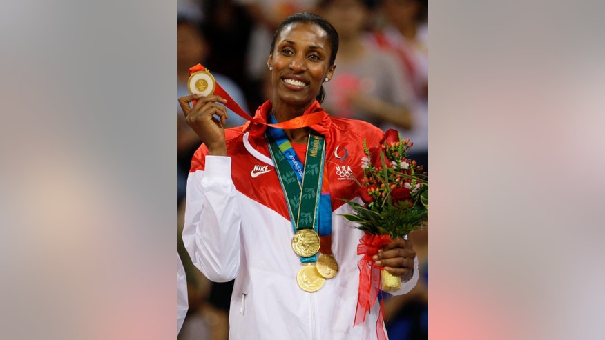 FILE - In this Aug. 23, 2008, file photo, USA player Lisa Leslie holds up the fourth of her gold medals after receiving gold for beating Australia in the women's basketball gold medal game at the Beijing 2008 Olympics in Beijing. Leslie headlines the 2015 women's basketball Hall of Fame induction class announced Saturday, July 19, 2014,  She is joined by former Houston Comets star Janeth Arcain, University of Georgia standout Janet Harris, former Duke coach Gail Goestenkors, longtime Oregon high school coach Brad Smith and Oklahoma State coach Kurt Budke, who was killed in a plane crash in 2011.  (AP Photo/Dusan Vranic, File