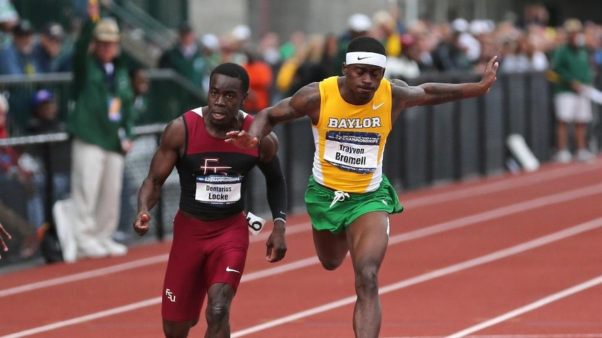 FILE - In this June 13, 2014, file photo, Baylor's Trayvon Bromell, right, and Florida State's Dentarius Locke race to the finish line during the men's 100 meters race at the NCAA track and field championships, in Eugene, Ore. The Baylor freshman set a junior world record in the 100 meters at the NCAA track and field championships last month. He broke the 10-second barrier, running in 9.97 at Hayward Field. Bromell is making bold predictions for the junior world track championships this week. (AP Photo/Rick Bowmer, File)