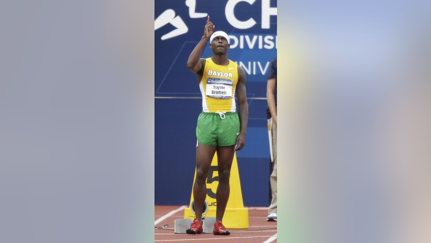 In this June 13, 2014, photo, Baylor's Trayvon Bromell points skyward before the start of the men's 100 meters at the NCAA track and field championships, in Eugene, Ore. The Baylor freshman set a junior world record in the 100 meters at the NCAA track and field championships last month. He broke the 10-second barrier, running in 9.97 at Hayward Field. Bromell is making bold predictions for the junior world track championships this week. (AP Photo/Rick Bowmer)