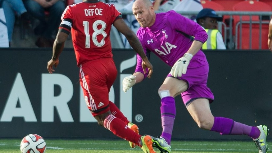 Tottenham Hotspur's keeper Brad Friedel, right, makes a save on Toronto FC's Jermain Defoe during the first half of a friendly soccer match in Toronto on Wednesday, July 23, 2014. (AP Photo/The Canadian Press, Darren Calabrese)