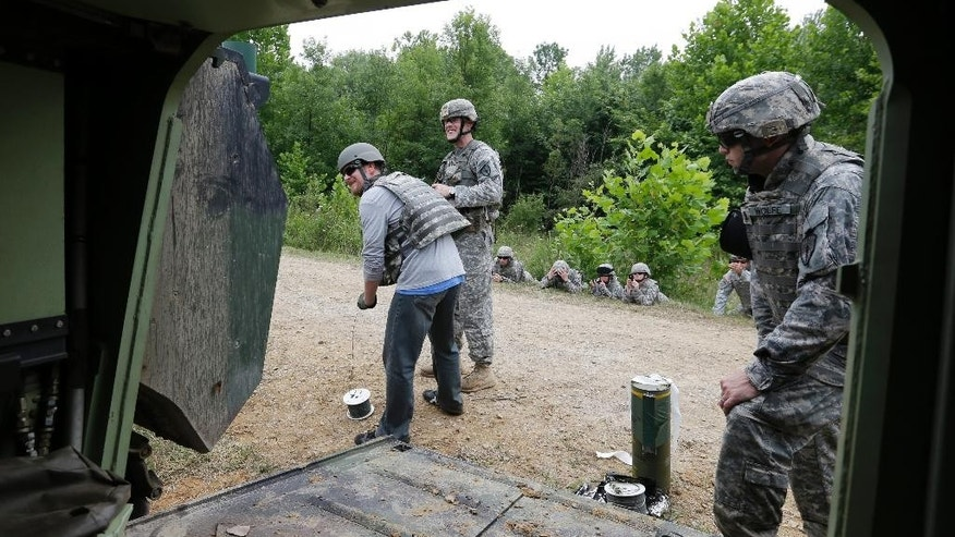 NASCAR driver Dale Earnhardt Jr., center, pulls a firing pin during a C4 demolition exercise at Camp Atterbury Wednesday, July 23, 2014, in Edinburgh, Ind. (AP Photo/Darron Cummings)