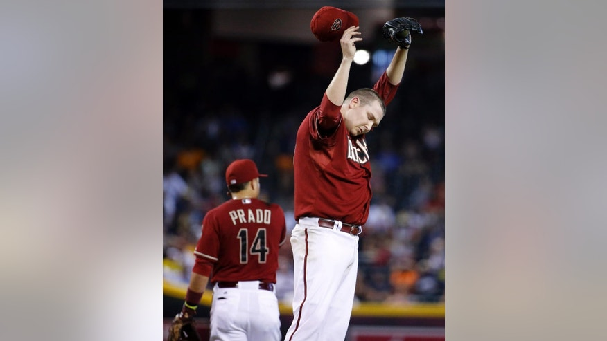 Arizona Diamondbacks pitcher Trevor Cahill wipes his head during the fourth inning of a baseball game against the Detroit Tigers, Wednesday, July 23, 2014, in Phoenix. (AP Photo/Matt York)