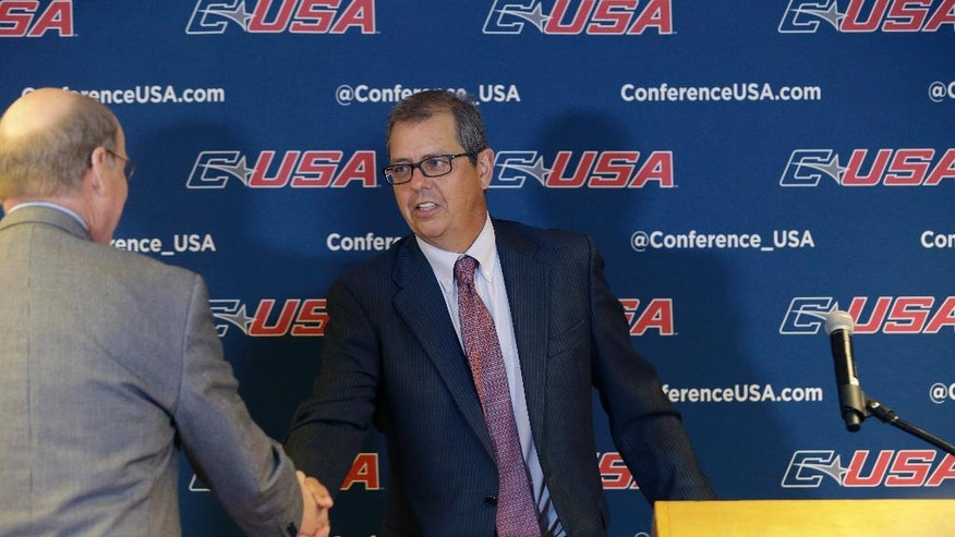 Conference USA commissioner Britton Banowsky, right, shakes hands with College Football Playoff executive director Bill Hancock during the NCAA college Conference USA football media day in Irving, Texas Wednesday, July 23, 2014. Banowsky seems to be settling in after a few years of significant change in the makeup of its league, at the same time the five power conferences seem so close to the autonomy they have sought. (AP Photo)