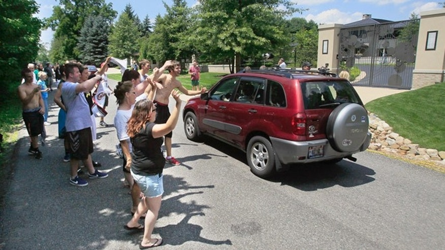 July 11, 2014: In this file photo, Cleveland Cavaliers basketball fans celebrate in front of the house of LeBron James, in Bath, Ohio, after learning of James' decision to sign as a free-agent with the Cavaliers.  (AP Photo/Akron Beacon Journal, Karen Schiely, File)