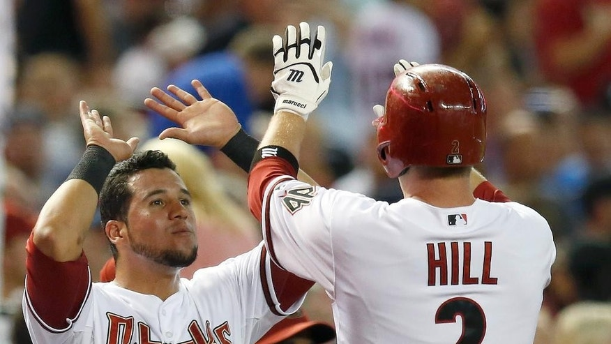 Arizona Diamondbacks' Aaron Hill (2) gets high-fives from teammate David Peralta after Hill hit a home run against the Detroit Tigers during the first inning of a baseball game on Tuesday, July 22, 2014, in Phoenix. (AP Photo)