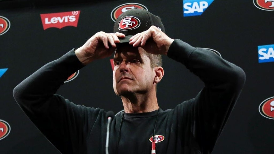 San Francisco 49ers head coach Jim Harbaugh adjust his cap as he answers questions from the media during an NFL football training camp on Thursday, July 24, 2014, in Santa Clara, Calif. (AP Photo)