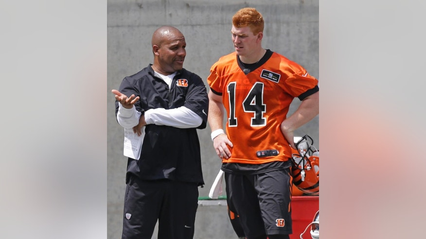 Cincinnati Bengals quarterback Andy Dalton (14) talks with offensive coordinator Hue Jackson during an NFL football organized team activity on Monday, June 16, 2014, in Cincinnati. Cincinnati opens training camp Thursday afternoon. (AP Photo)