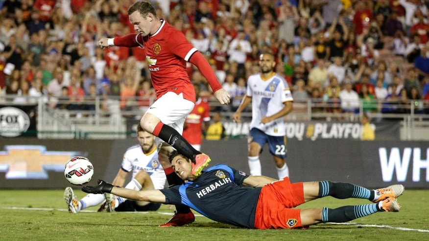 Manchester United's Wayne Rooney, top, scores past Los Angeles Galaxy goalkeeper Jaime Penedo during the first half of a friendly soccer match at Rose Bowl on Wednesday, July 23, 2014, in Pasadena, Calif. (AP Photo)