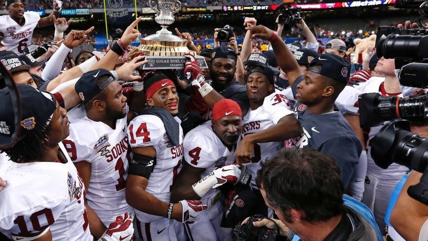 FILE - In this Jan. 3, 2014 file photo, Oklahoma holds up the Sugar Bowl trophy after defeating Alabama 45-31 in the NCAA college football matchup in New Orleans. It now seems like forever since Oklahoma defeated Alabama in the Sugar Bowl. The hype around the program has been building ever since.  (AP Photo/Rusty Costanza, File)