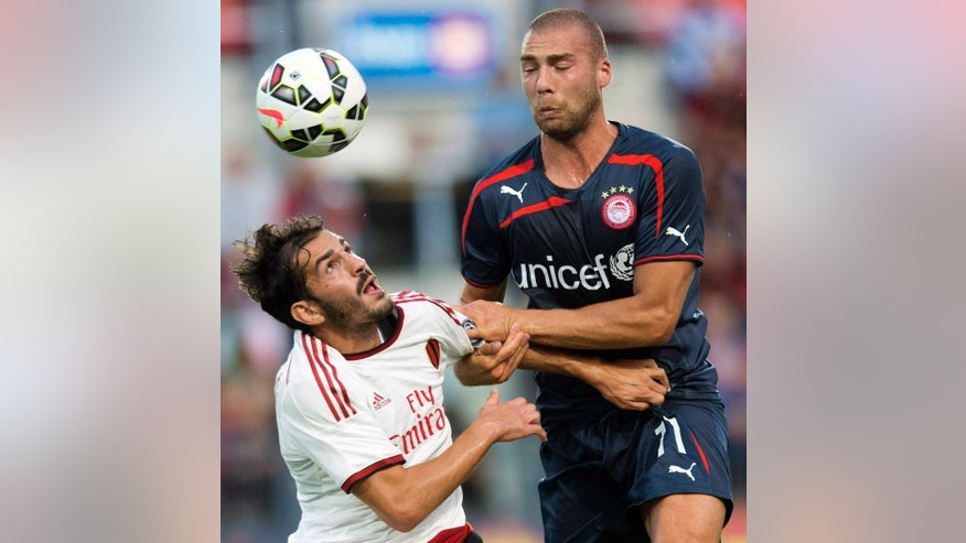 AC Milan's Riccardo Saponara, left, and Olympiacos' Patjim Kasami battle for the ball during the first half of an International Champions Cup soccer match at BMO Field in Toronto on Thursday, July 24, 2014. (AP Photo/The Canadian Press, Darren Calabrese)