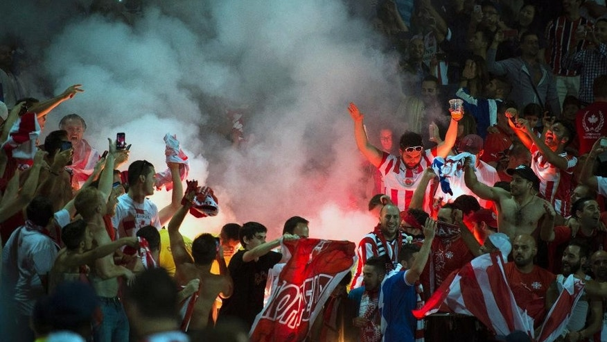 Olympiacos supporters light flares while celebrating their side's 3-0 victory over AC Milan in an International Champions Cup soccer match at BMO Field in Toronto on Thursday, July 24, 2014. (AP Photo/The Canadian Press, Darren Calabrese)