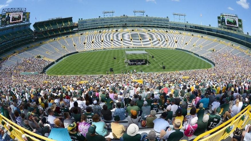 In this image taken with a  fish-eye lens, Green Bay Packers shareholders listen as president Mark Murphy addresses them from the stage inside Lambeau Field during the NFL football team's annual shareholders meeting Thursday, July 24 2014m in Green Bay, Wis. (AP Photo/The Green Bay Press-Gazette, Jim Matthews) NO SALES