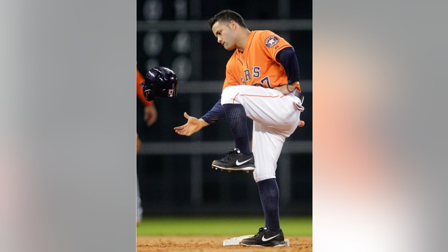 Houston Astros' Jose Altuve kicks his helmet after having a steal at second overturned for an out after video review, during the sixth inning of a baseball game against the Miami Marlins, Friday, July 25, 2014, in Houston. (AP Photo/Patric Schneider)