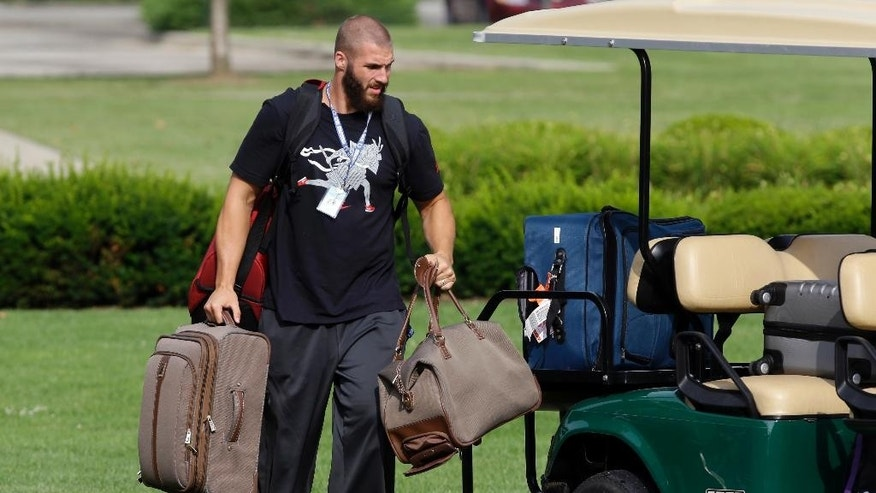 Indianapolis Colts linebacker Bjoern Werner, of Germany, carries his bags from a golf cart as the players arrived for the NFL team's football training camp in Anderson, Ind., Wednesday, July 23, 2014.  (AP Photo/Michael Conroy)