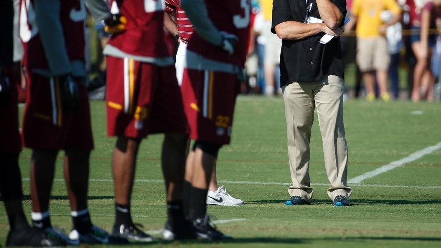 ESPN broadcaster and former NFL head coach Jon Gruden, right, watches the Washington Redskins practice at the team's NFL football training facility, Friday, July 25, 2014 in Richmond, Va. (AP Photo)