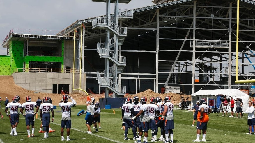 As a new facility rises in the background, Denver Broncos defensive players are shown during a morning session at the team's NFL football training camp in Englewood, Colo.,  on Friday, July 25, 2014. Because of the construction, Broncos officials have banned fans from attending training camp this year. (AP Photo)