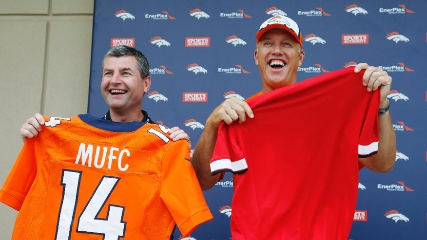 Denis Irwin, left, a member of Manchester United's legends, holds up a jersey after an exchange with John Elway, general manager of the Denver Broncos, during a morning session at the team's NFL football training camp in Englewood, Colo.,  on Friday, July 25, 2014. Manchester United visited the Broncos' trianing camp on Friday before playing in the Mile High City on Saturday. (AP Photo)