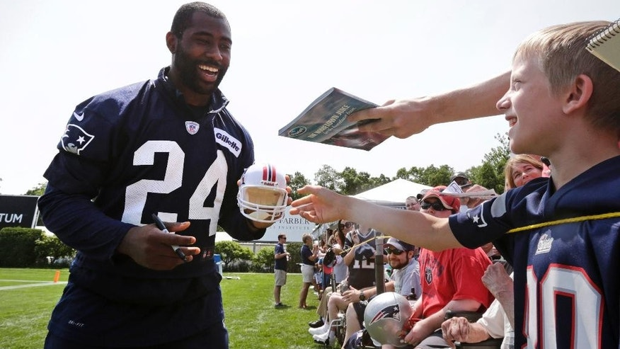 New England Patriots cornerback Darrelle Revis jokes with fans as he signs autographs after an NFL football training camp in Foxborough, Mass., Friday, July 25, 2014. (AP Photo)