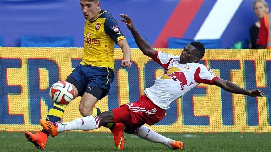 Arsenal forward Zak Ansah, left, controls the ball against New York Red Bulls defender Ambroise Oyongo during the second half of an international friendly soccer match Saturday, June 26, 2014, in Harrison, N.J. The Red Bulls won 1-0. (AP Photo/Adam Hunger)