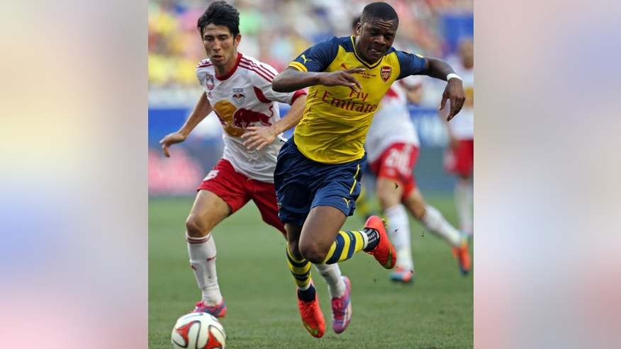 Arsenal forward Chuba Akpom, right, trips in front of New York Red Bulls defender Kosuke Kimura, left, during the second half of an international friendly soccer game on Saturday, June 26, 2014, in Harrison, N.J. The New York Red Bulls defeated Arsenal 1-0. (AP Photo/Adam Hunger)