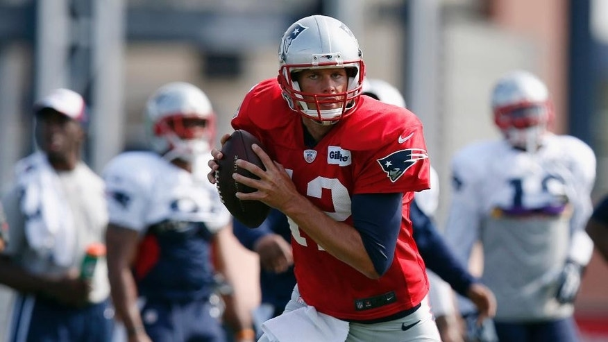 New England Patriots quarterback Tom Brady carries the ball during NFL football training camp in Foxborough, Mass., Saturday, July 26, 2014. (AP Photo)