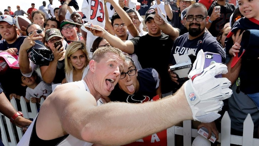 Houston Texans defensive end J.J. Watt, left, takes a selfie with Nina Munduia after an NFL football training camp practice on Saturday, July 26, 2014, in Houston. (AP Photo/David J. Phillip)