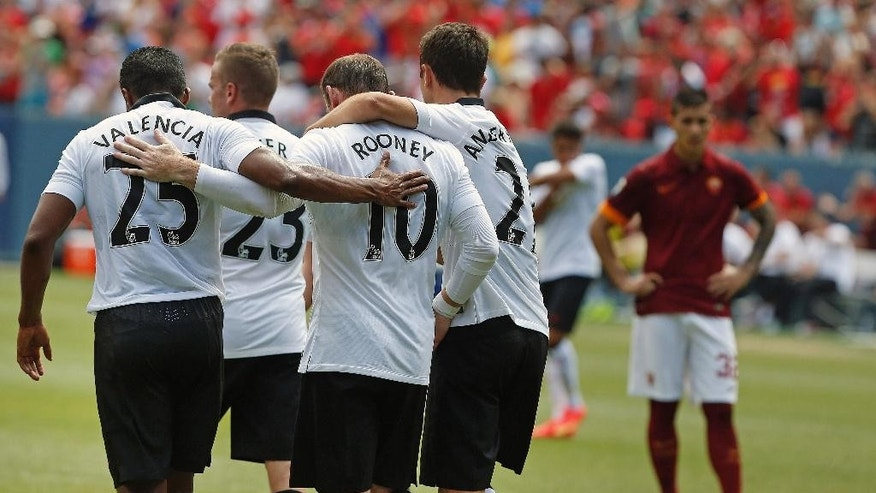 Manchester United players hug after a goal by Wayne Rooney during the first half of an exhibition soccer match against AS Roma at Mile High Stadium, in Denver, Saturday, July 26, 2014. (AP Photo/Brennan Linsley)
