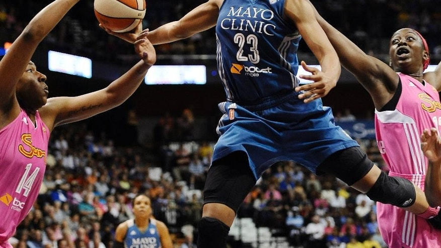 Minnesota Lynx's Maya Moore, center, glides to the basket as Connecticut Sun's Kelsey Bone, left, and Chiney Ogwumike, right, defend during the second half of a WNBA basketball game, Sunday, July 27, 2014, in Uncasville, Conn. The Lynx won 76-65. (AP Photo/Jessica Hill)