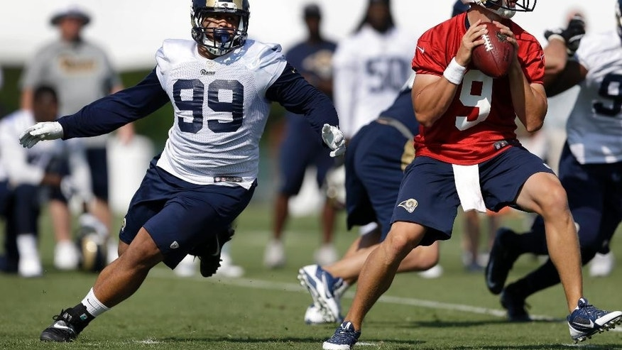 St. Louis Rams defensive tackle Aaron Donald, left, tries to get to quarterback Austin Davis during training camp at the NFL football team's practice facility Friday, July 25, 2014, in St. Louis. (AP Photo/Jeff Roberson)