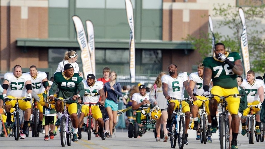 Green Bay Packers players ride bikes to NFL football training camp Monday, July 28, 2014, in Green Bay, Wis. (AP Photo/Morry Gash)