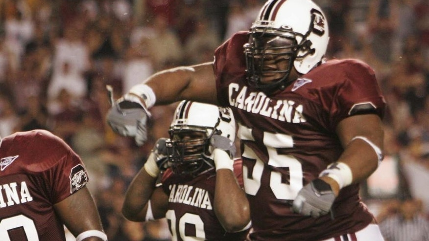 FILE - In this Sept. 1, 2005 file photo, South Carolina's Stanley Doughty (55) celebrates with his teammates after stopping Central Florida from scoring during an NCAA college football game in Columbia, S.C. Doughty is one of the plaintiffs in a class-action head injury lawsuit working its way through federal court in Chicago. The NCAA and the plaintiffs announced a settlement on Tuesday, July 29, 2014.  (AP Photo/Perry Baker, File)