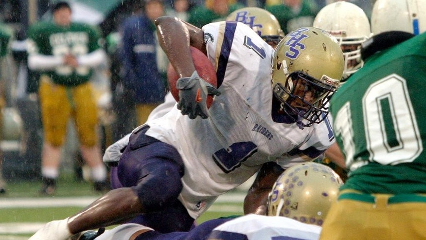 FILE - In this Nov. 27, 2004 file photo, Bloomington High School running back Adrian Arrington tries to clear a pile of Providence Catholic defenders during the Class 6A championship football game in Champaign, Ill. Arrington, who later went on to play at Eastern Illinois in Charleston, is the lead plaintiff in a class-action head injury lawsuit working its way through federal court in Chicago. The NCAA and the plaintiffs announced a settlement on Tuesday, July 29, 2014. (AP Photo/ Stephen Haas, File)