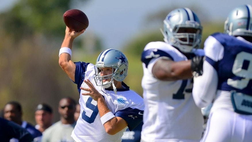 Dallas Cowboys quarterback Tony Romo (9) throws a pass as the offense runs a play during NFL football training camp on Saturday, July 26, 2014, in Oxnard, Calif. (AP Photo/Gus Ruelas)