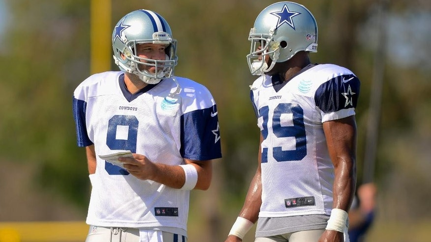 Dallas Cowboys quarterback Tony Romo (9) and running back DeMarco Murray (29) talk things over during the NFL football team's training camp, Saturday, July 26, 2014, in Oxnard, Calif. (AP Photo/Gus Ruelas)