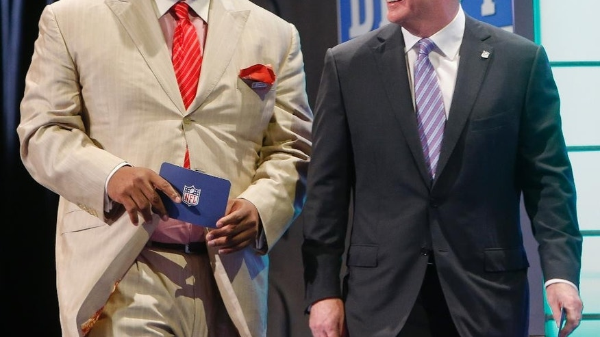 FILE - In this May 9, 2014 file photo, former Seattle Seahawks linebacker Walter Jones, left, walks out on stage with NFL commissioner Roger Goodell to announce the Seahawks pick for the second round of the 2014 NFL Draft in New York. Jones will be inducted into the Pro Football Hall of Fame in Canton, Ohio on Saturday, Aug. 2, 2014. (AP Photo/Jason DeCrow, File)