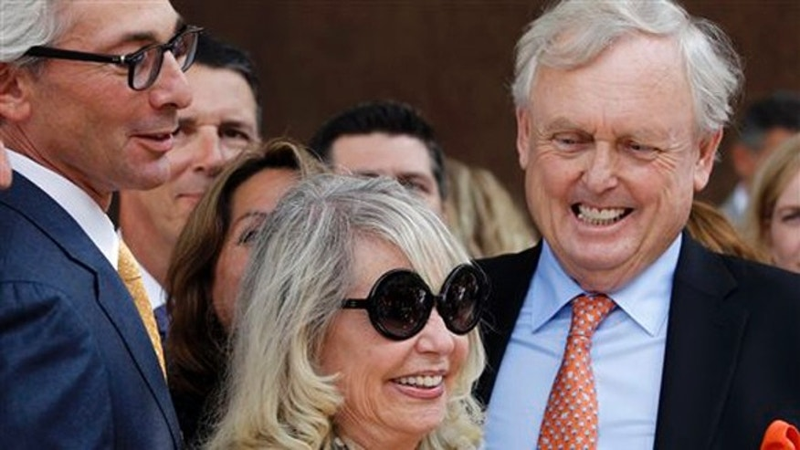 With her attorney Pierce O'Donnell, right, Shelly Sterling, center, smiles as she talks to reporters after a judge ruled in her favor and against her estranged husband, Los Angeles Clippers owner Donald Sterling, in his attempt to block the $2 billion sale of the NBA basketball team, outside Los Angeles Superior Court Monday, July 28, 2014.
