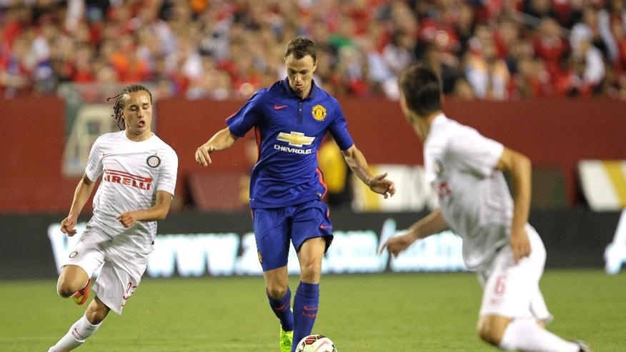 Manchester United's Jonny Evans, center, moves the ball as Inter Milan's Diego Laxalt, left, and Marco Andreolli (6) defend during the second half of the 2014 Guinness International Champions Cup soccer game, Tuesday, July 29, 2014, in Landover, Md. Manchester United won in a 5-3 penalty kick shootout. (AP Photo/Luis M. Alvarez)